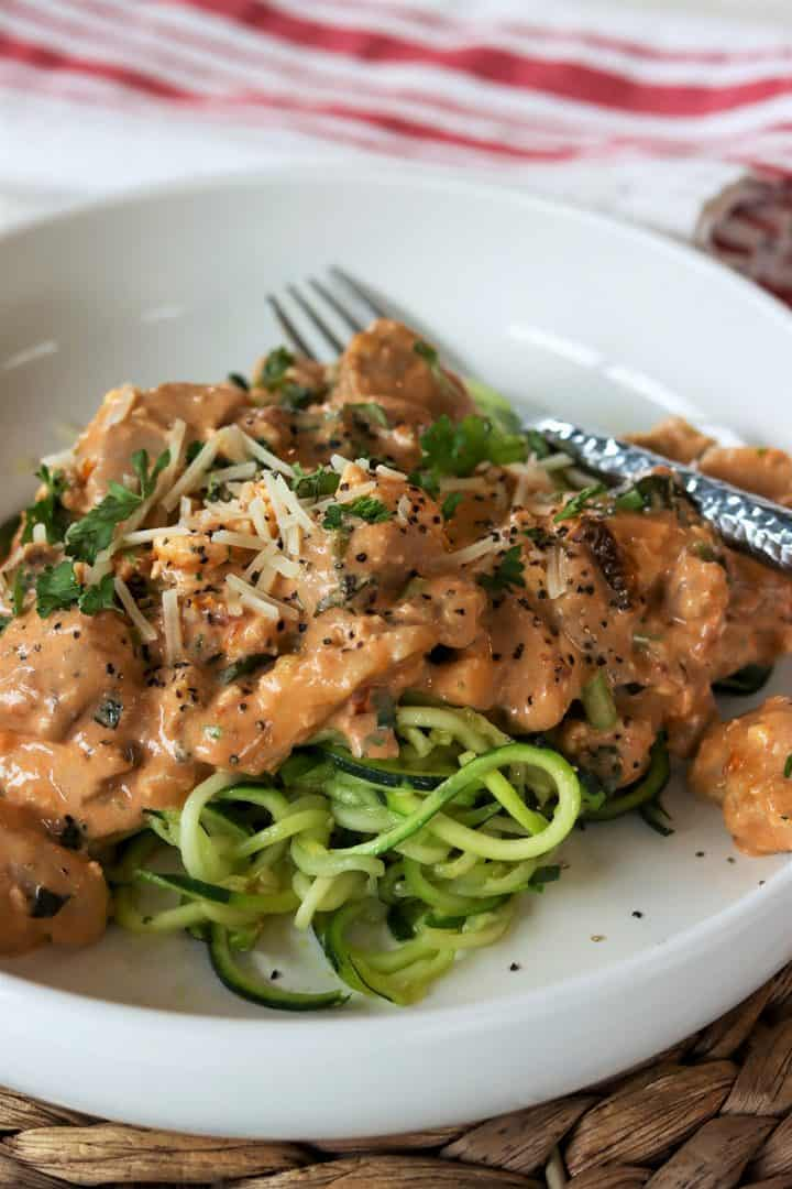 Portrait image of low carb chicken in tomato basil cream sauce served on a white plate over zucchini noodles and garnished with extra cheese and parsley.