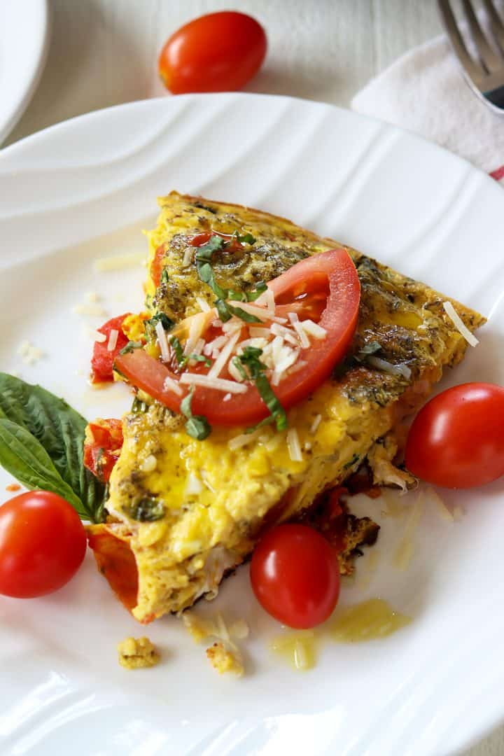 Portrait image of a slice of tomato mozzarella caprese frittata on a white plate garnished with basil, tomato, and cheese
