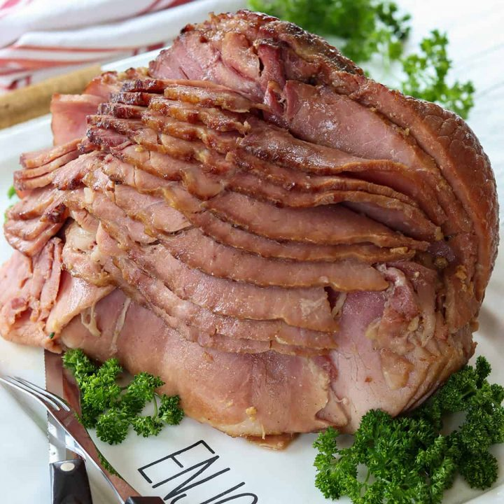 Feature image of brown sugar bourbon glazed ham served on a white platter and garnished with parsley.