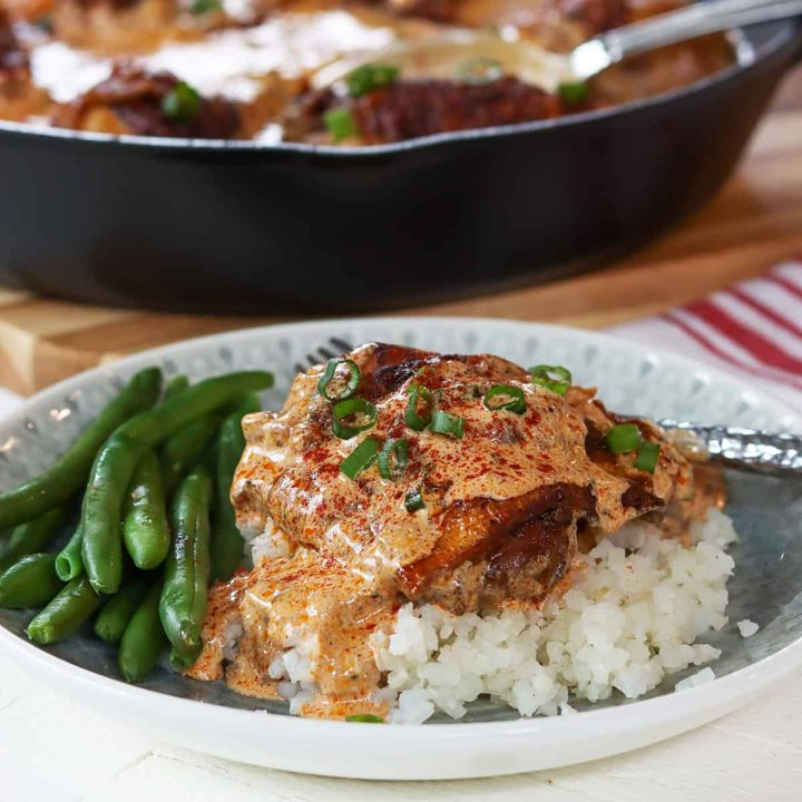 Feature image of Hungarian Paprika chicken served on a white and gray plate and garnished with green onion.