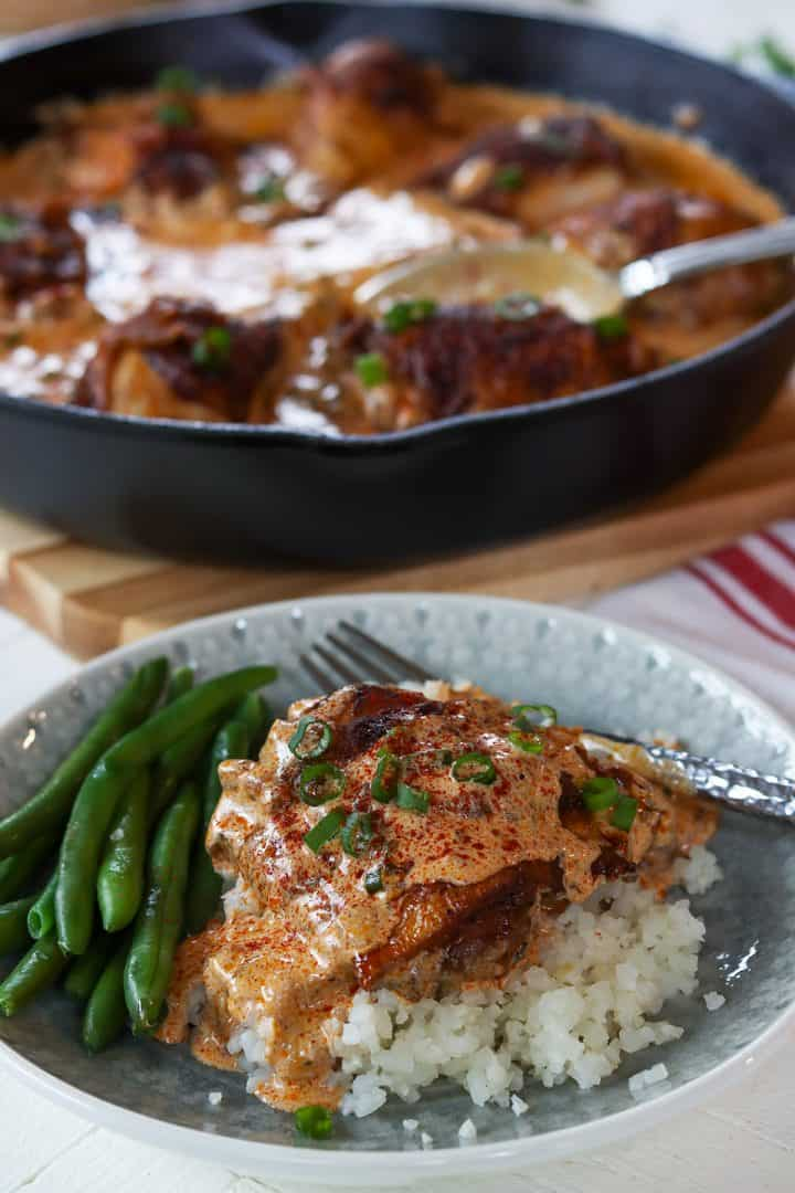 portrait image of hungarian paprka chicken served over riced cauliflower with a side of green beans. A skillet is in the background ready to serve up the next dish.