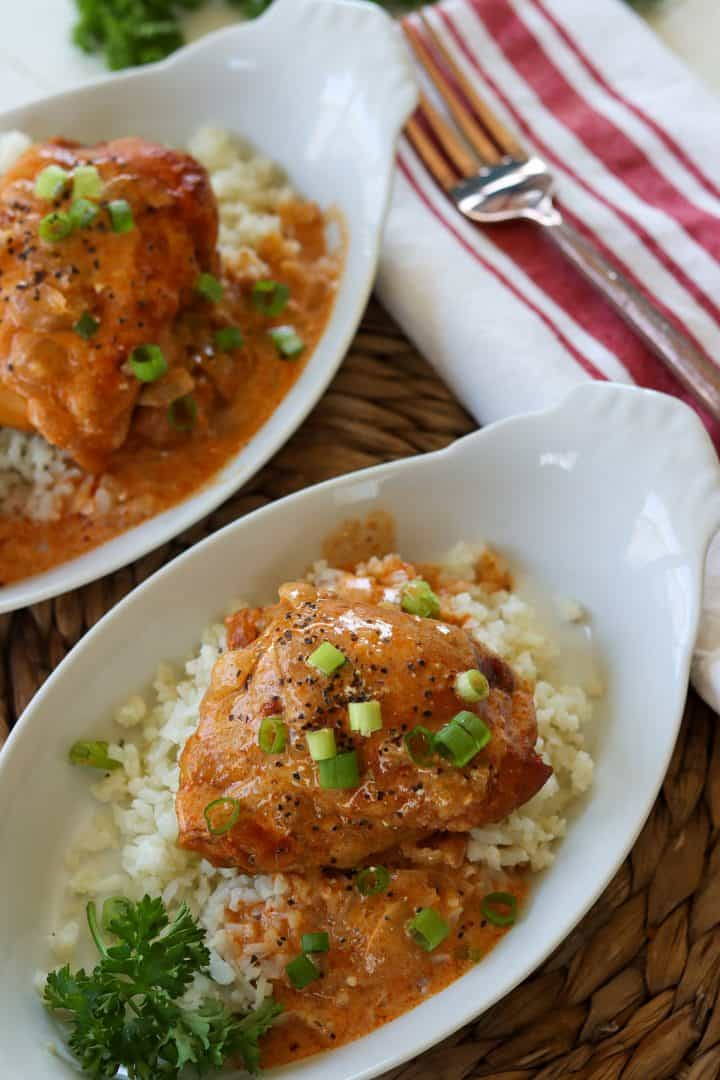 portrait image of slow cooker chicken paprika served in individual white dishes over riced cauliflower and garnished with green onion, parsley, and pepper.