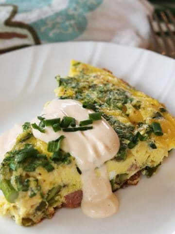 Square feature image of eggs benedict frittata served on a white plate and garnished with hollandaise and chives.