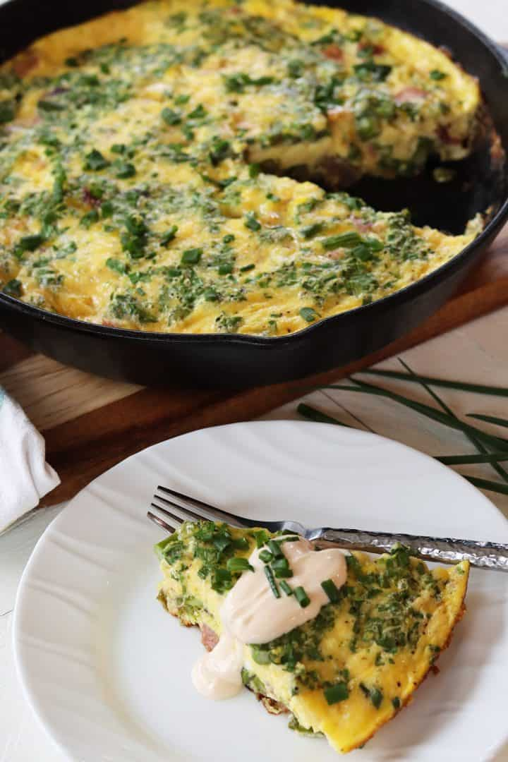 Portrait image featuring eggs benedict frittata in a cast iron skillet with one slice served on a white plate and drizzle with mock hollandaise sauce and garnished with chives.