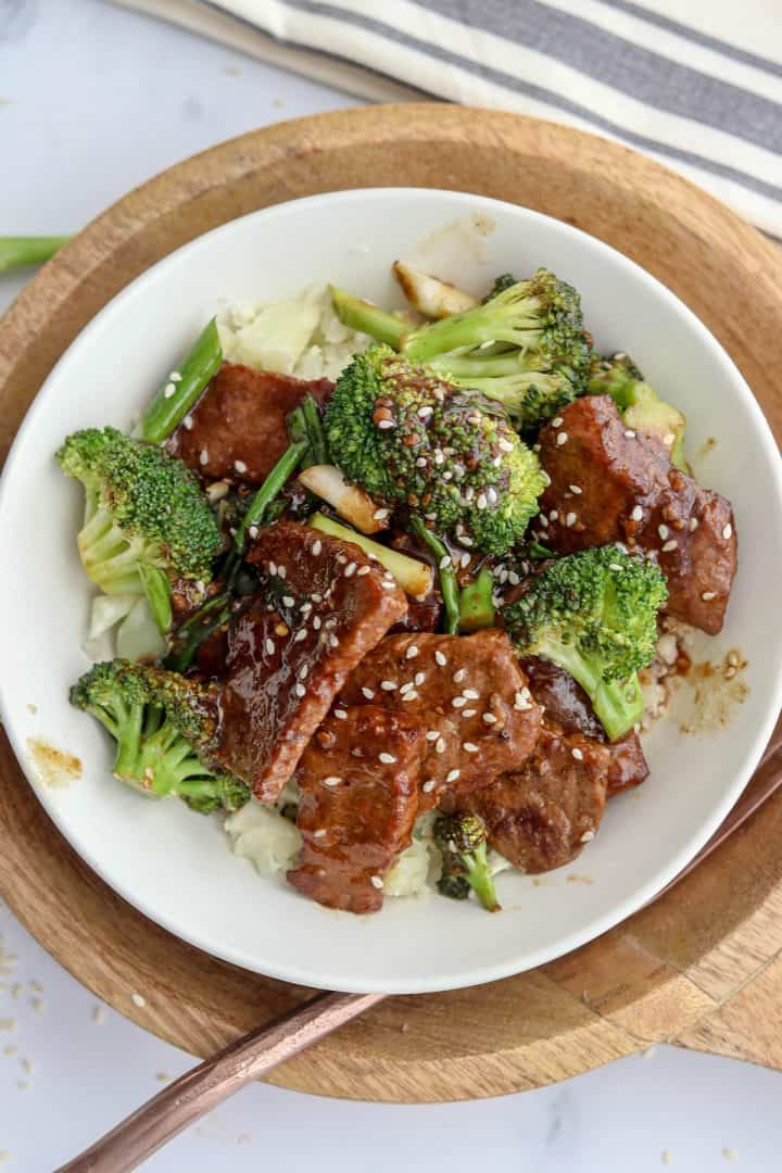 Mongolian beef served in a white bowl and garnished with extra Asian sauce and sesame seeds.