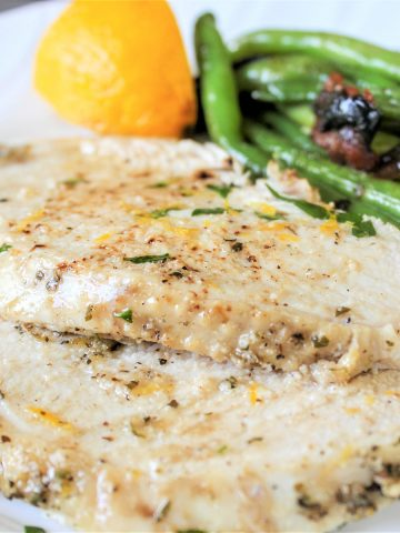 Square feature image of juicy tuscan turkey breast slices served on a white plate and garnished with fresh herbs and lemon zest