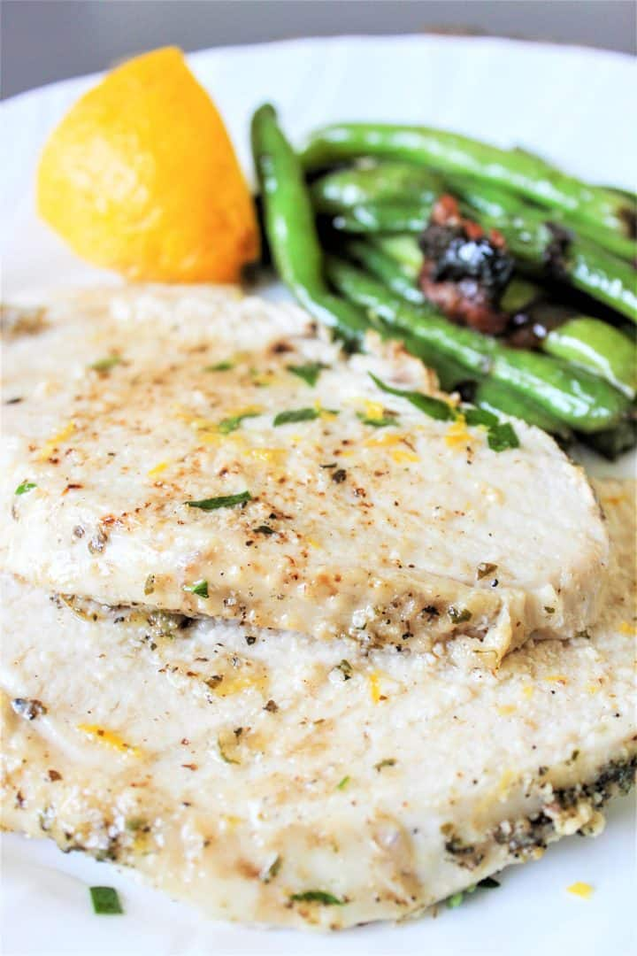 Tender slices of Tuscan turkey breast served on a white plate with a side of green beans and a lemon wedge.
