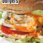 Pinterest pin with a a closeup side view of all the delicious layers in our juicy buffalo chicken burger. The burger is dripping with blue cheese dressing and buffalo wing sauce.