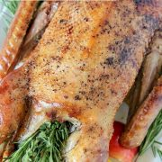 Pinterest pin with an image of a full cooked roast goose served on a platter.