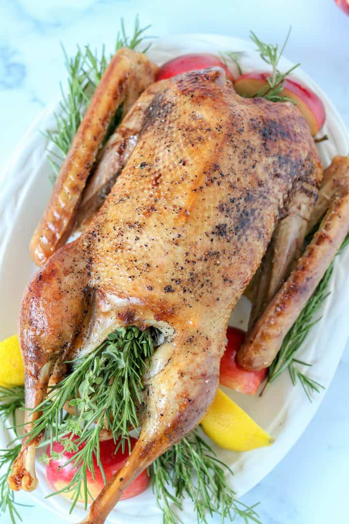 Portrait image of a roasted goose served on a white platter and surrounded by sprigs of fresh herbs, red apples, and lemons.
