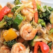 Pinterest pinnable image of keto shrimp stir fry served on a white plate - lot's of veggies, shrimp, and a delicious healthy homemade stir fry sauce.