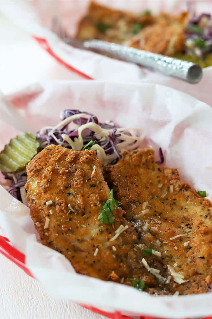 A golden piece of parmesan crusted tilapia in a red basket lined with white parchment paper with a side of coleslaw and pickles.
