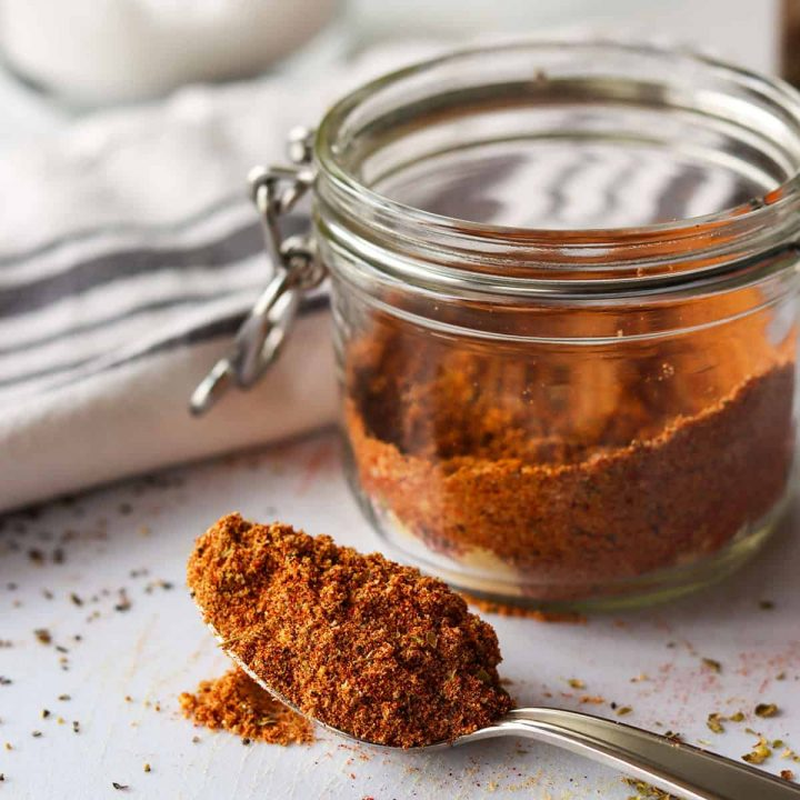 a jar full of premade fajita seasoning mix with a spoon full of seasoning on a cutting board.