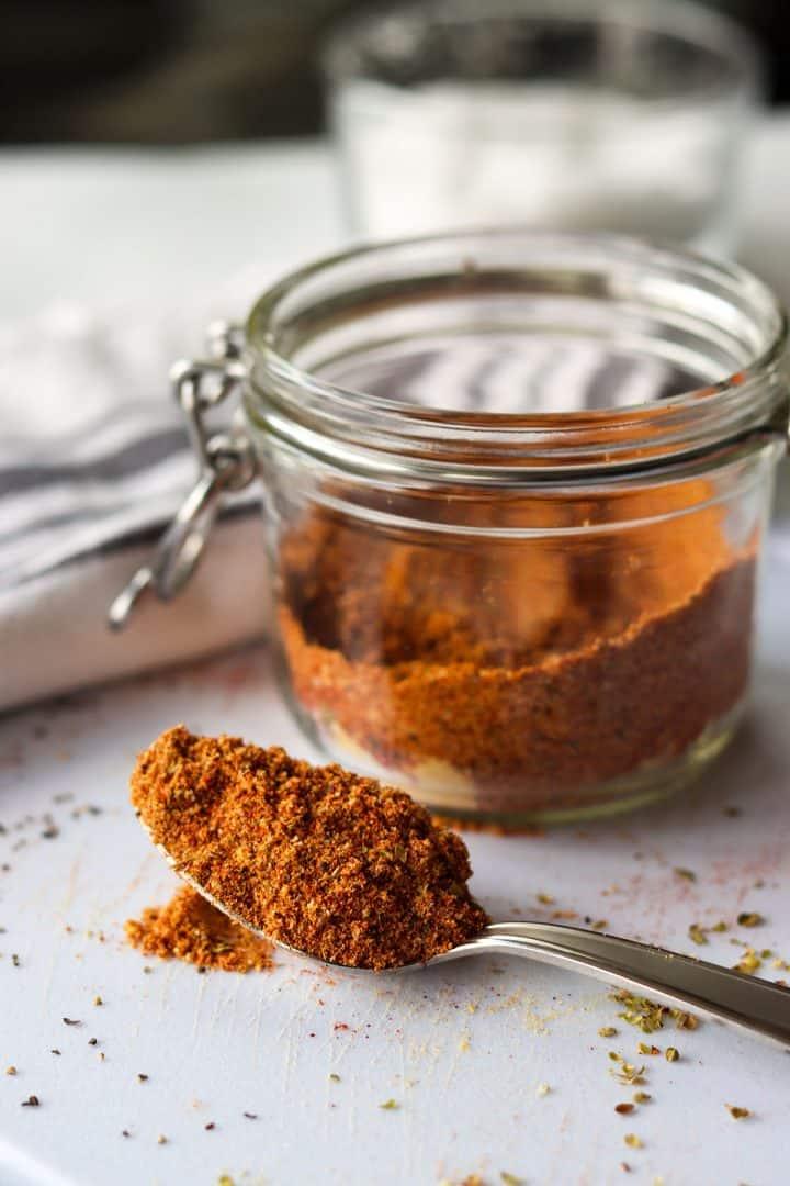 fajita seasoning premade in a jar with a spoonful sitting on a cutting board