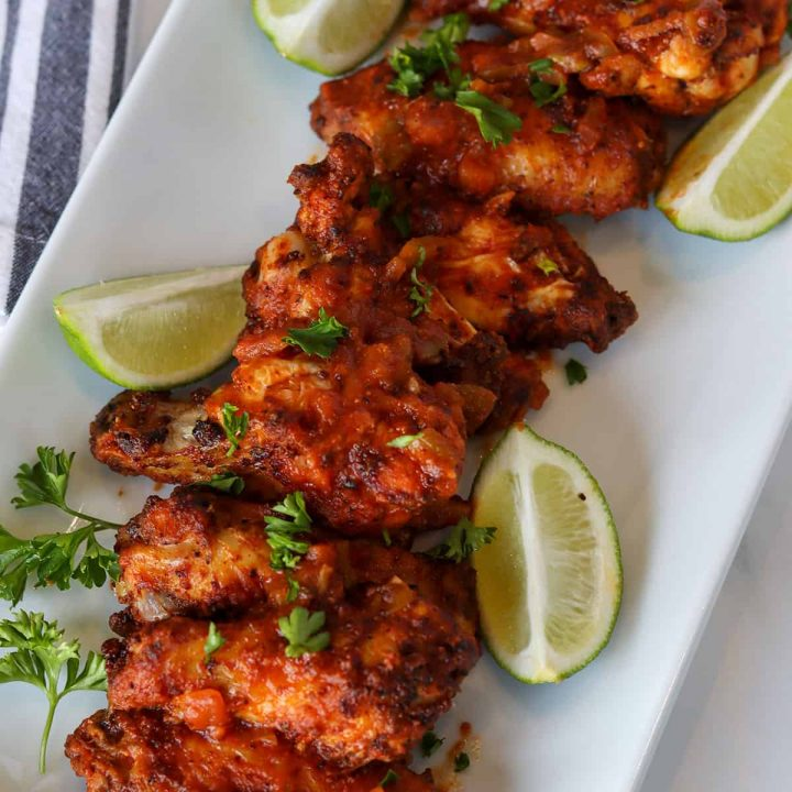 chicken wings served on a white platter with a garnish of fresh limes and parsley