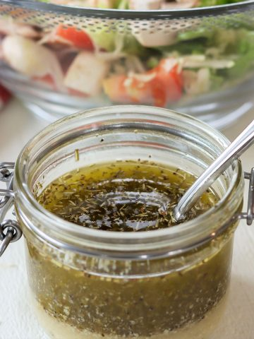 square image of homemade low carb italian dressing with a spoon ready to serve over your green salad