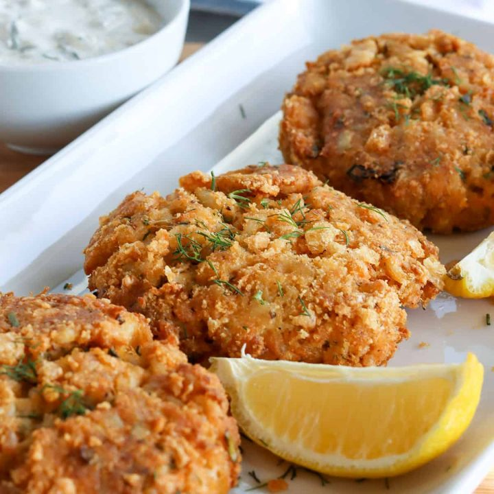 Air fryer crab cakes served on a white platter with lemon wedges and creamy dill dressing for dipping.