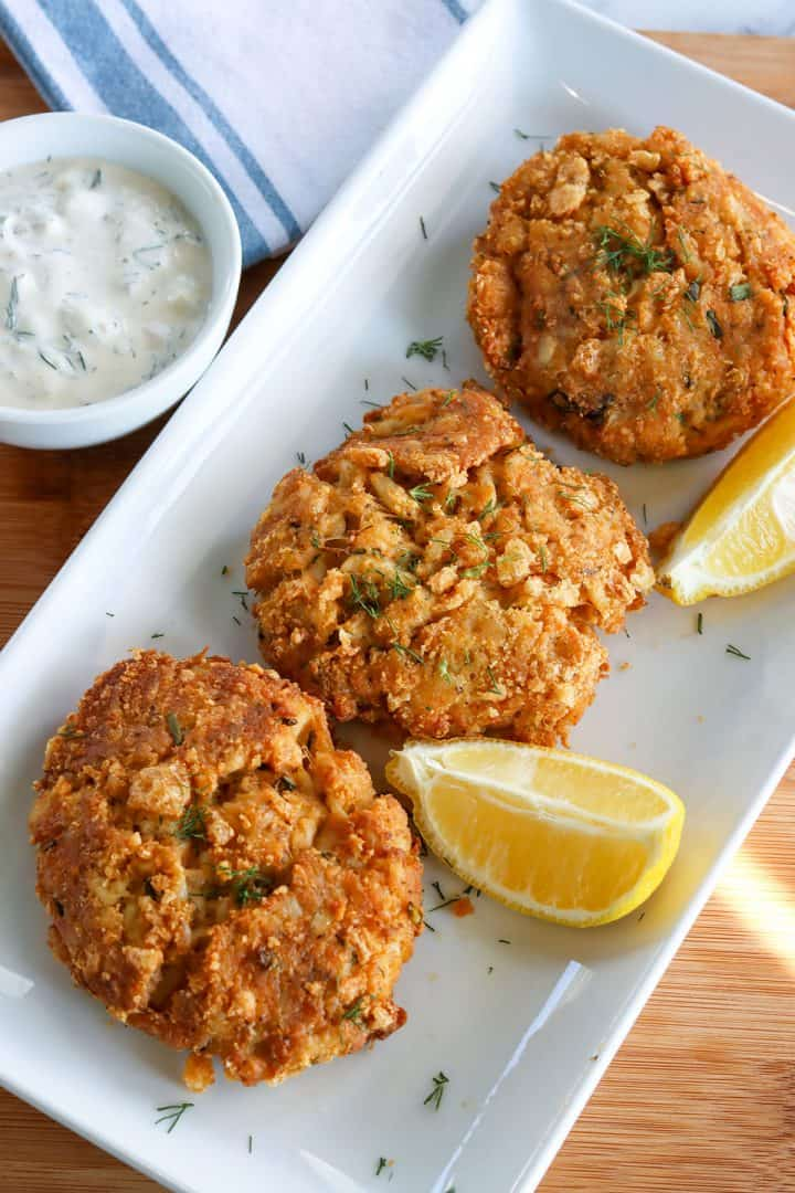 Three crabcakes served on a white rectangle plate with slices of lemon and a dish of dill sauce for dipping.