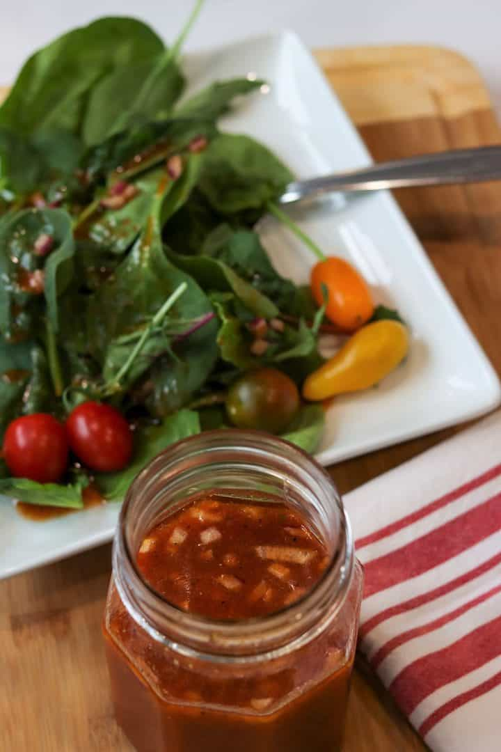portrait image of a mason jar full of homemade sugar free french dressing with a green salad with tomatoes in the background