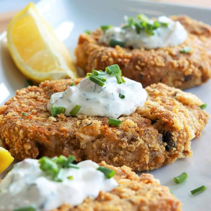 Close up view of an air fried salmon patty perfectly cooked and golden and garnished with dill sauce, chives, and lemon wedges.