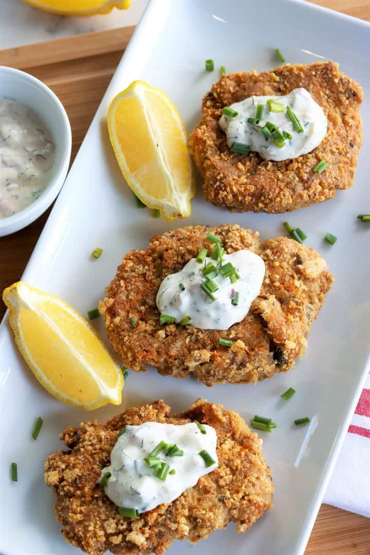 Three golden salmon patties on a white platter, served with a dollop of dill sauce and a side of lemon wedges