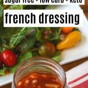 an image of french dressing in a mason jar with a side salad in the background.