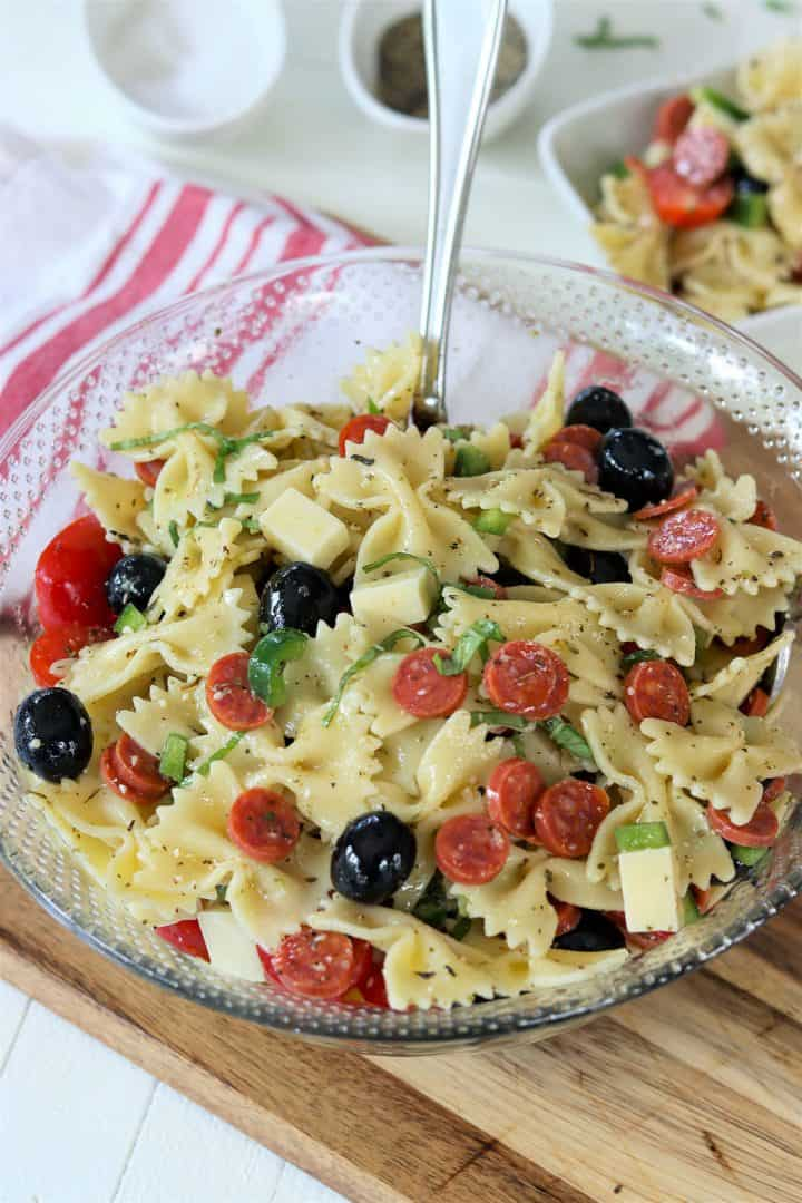 A clear glass bowl full of italian pasta salad garnished with fresh basil