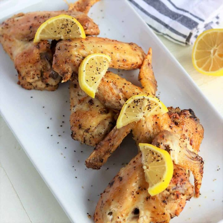 Lemon pepper wings served on a white platter and garnished with lemon slices and ground pepper.