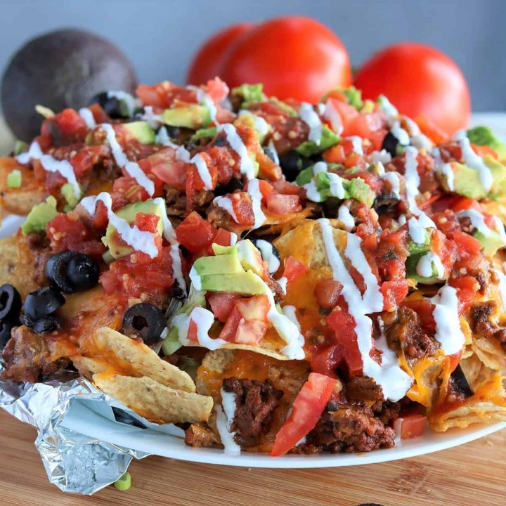 Piled high nachos with ground beef and loaded with toppings.