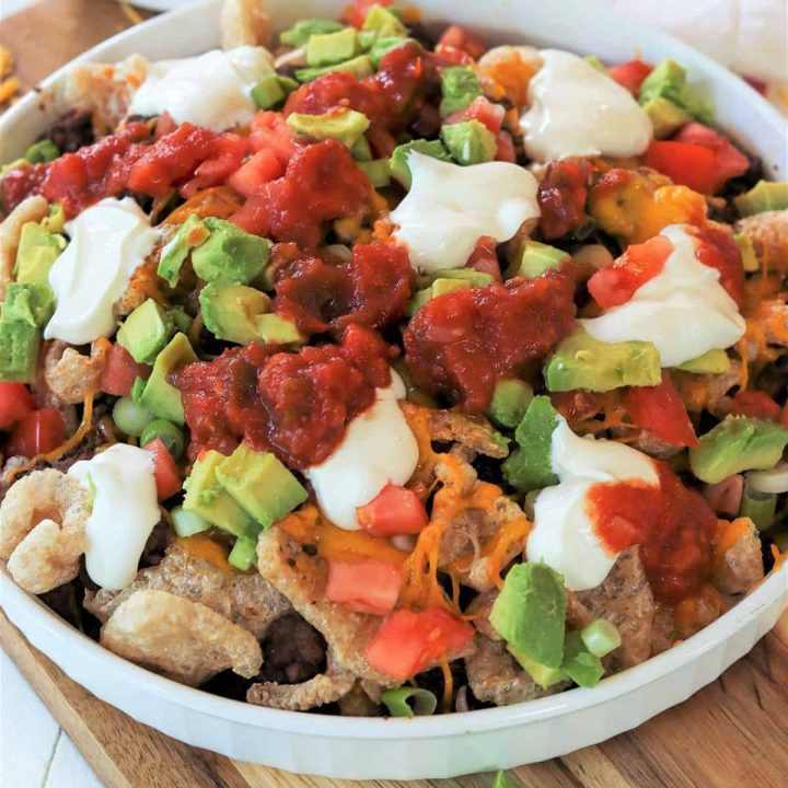 nachos piled high with toppings such as cheese, meat, olives, sour cream, salsa, avocado