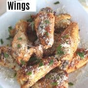 Pinterest pin with a plate full of garlic parmesan wings just out of the air fryer and ready to eat.