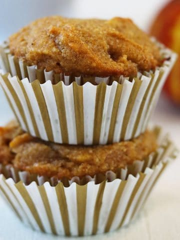 square feature image of two gluten free pumpkin muffins stacked on top of each other with a small pumpkin in the background.