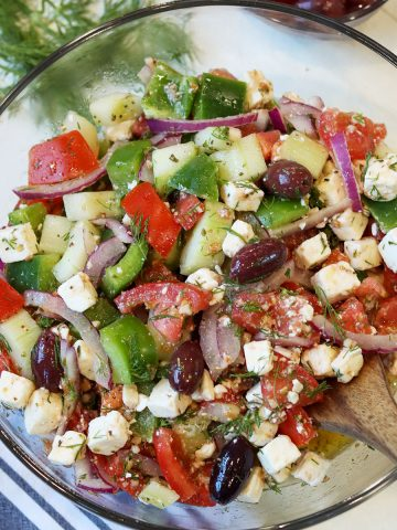 Greek salad served in a clear glass bowl and garnished with fresh dill.