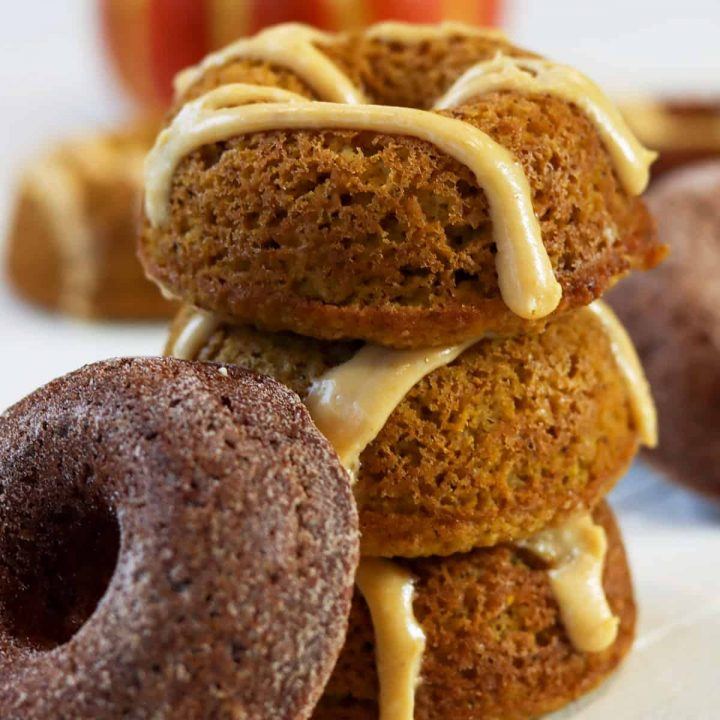 Three healthy pumpkin spice donuts stacked on top of each other.