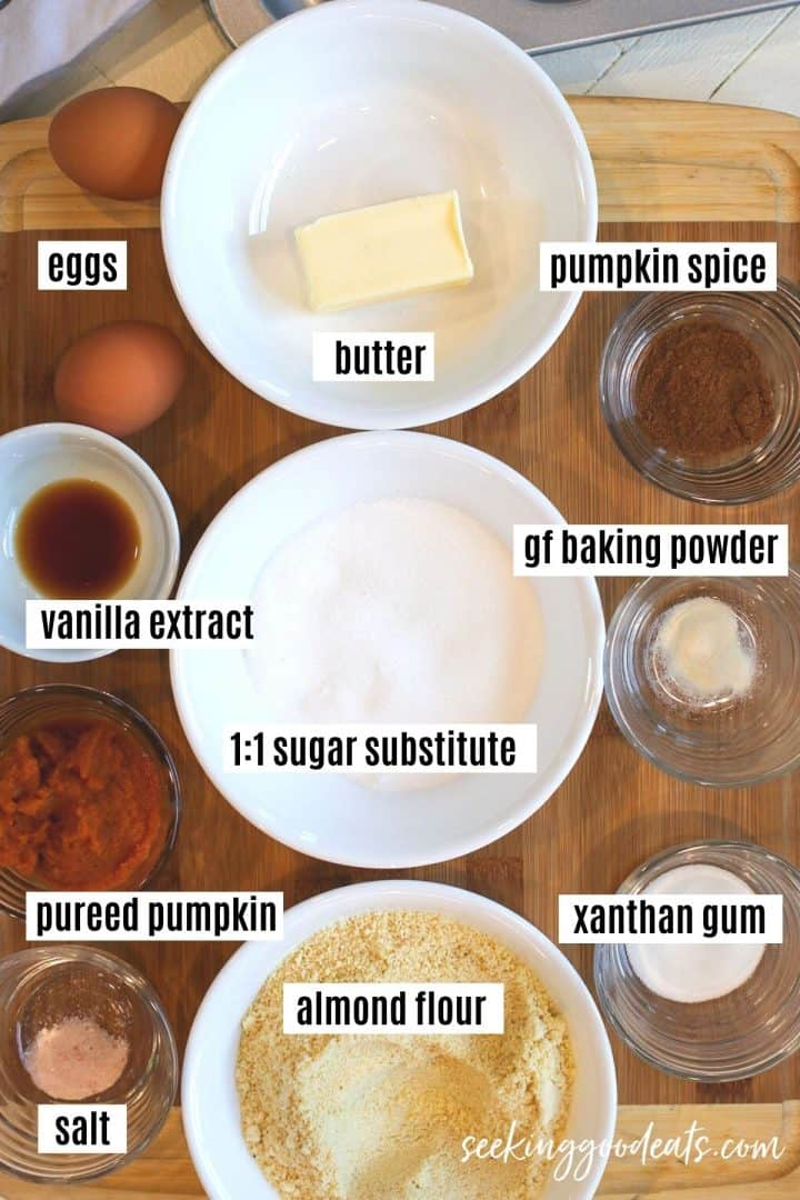 Ingredients needed to make pumpkin spice donuts on a wooden board