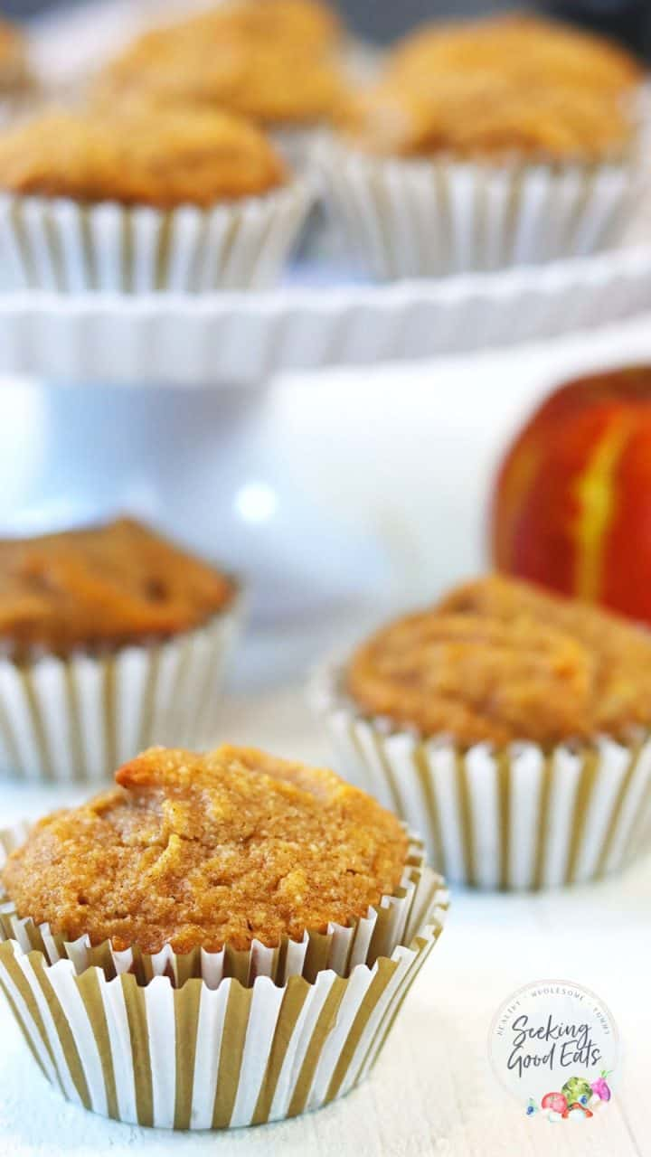 pumpkin muffins served on a white wood table and a fluted tiered cake plate. A small pumpkin is in the background