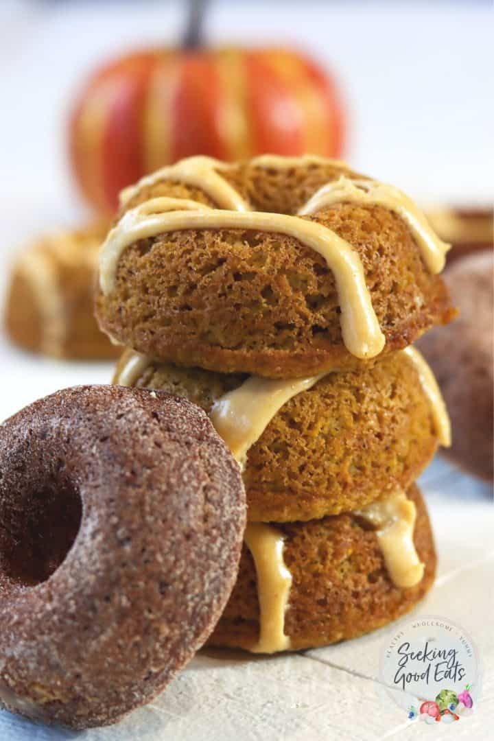 Pumpkin spice donuts stacked on top of each other on a white wooden board. A pumpkin is in the background