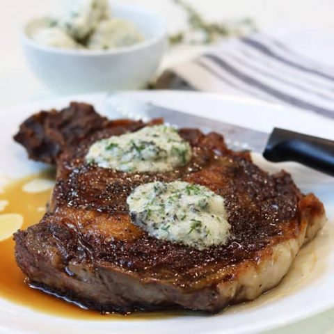 Ribeye steak with slowly melting garlic butter for steak served on a white plate.