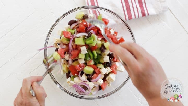 tossing greek salad ingredients in a clear glass bowl