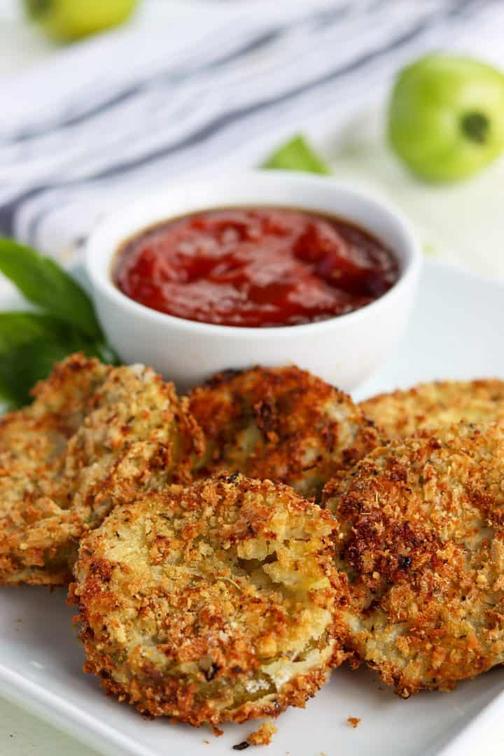 Fried green tomatoes served on a white plate with a small bowl of ketchup dipping sauce