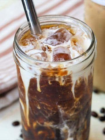 iced cold brew coffee served in a clear glass and topped with cream