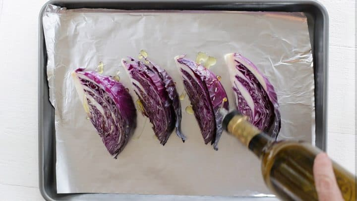 Seasoning cabbage with olive oil, salt, and pepper