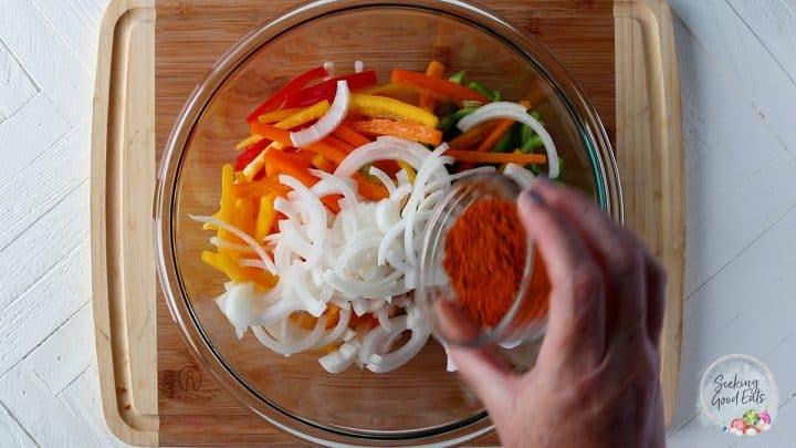 Seasoning chicken and vegetables with fajitas seasoning