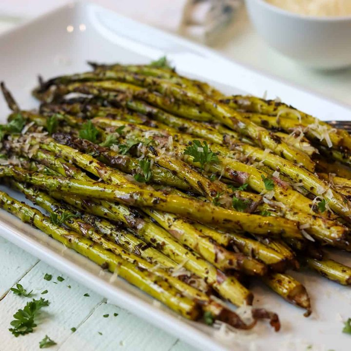 Asparagus served on a white plate with extra parmesan cheese and fresh parsley