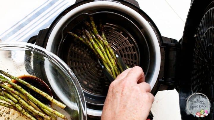 Placing asparagus into an air fryer basket