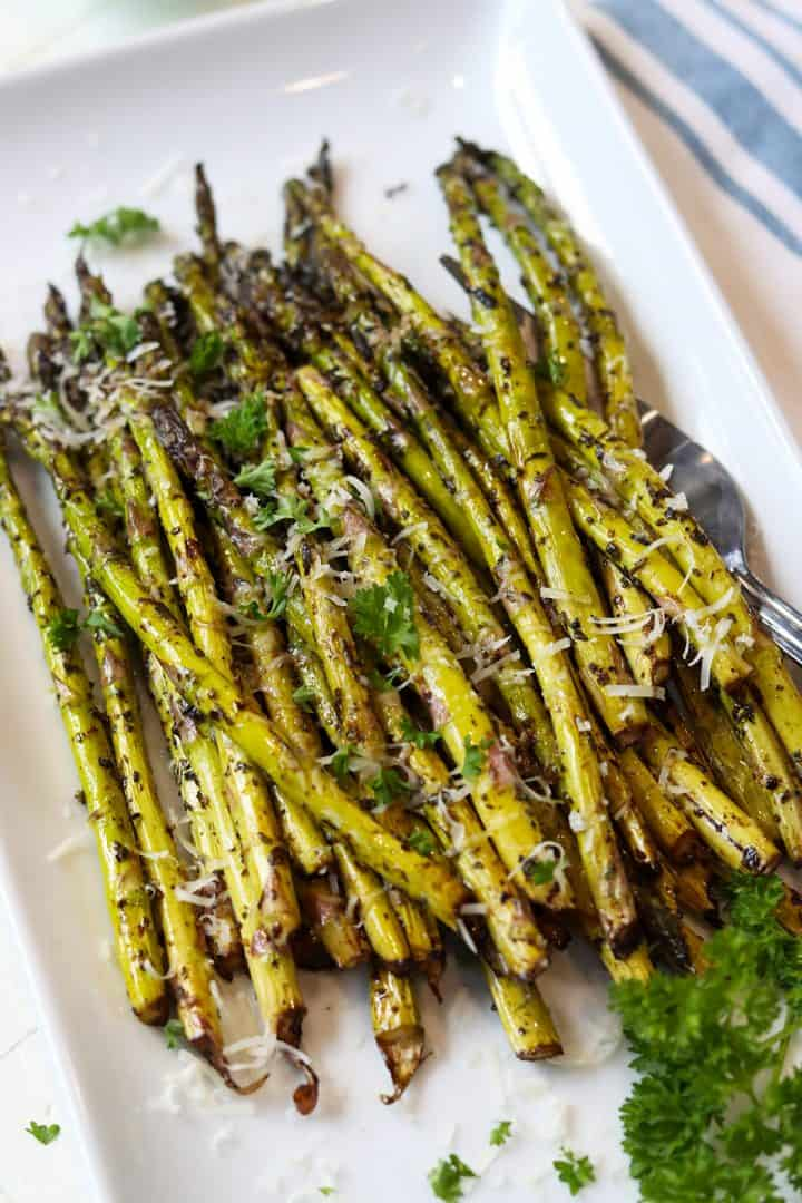 Air fried asparagus spears served on a white platter and garnished with parmesan cheese and parsley