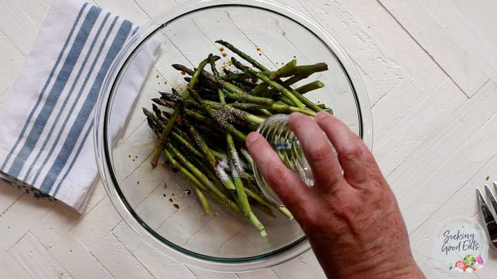 Tossing asparagus spears with seasonings in a clear glass bowl