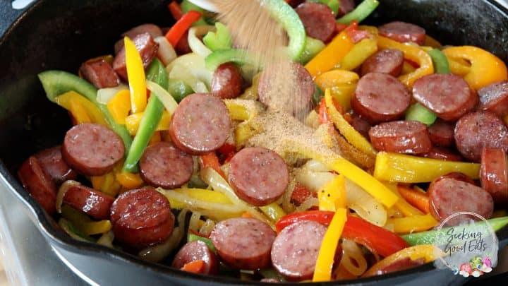 Mixing Cajun seasoning into sausage and vegetables