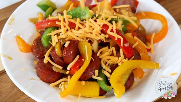 Serving and topping sausage and peppers with cheese