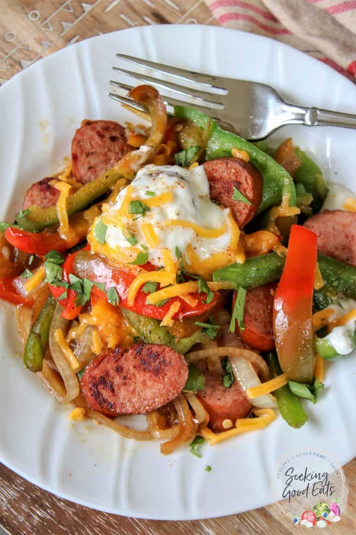 Keto sausage and peppers on a white plate garnished with sour cream and cheese and seasoning with Cajun spices
